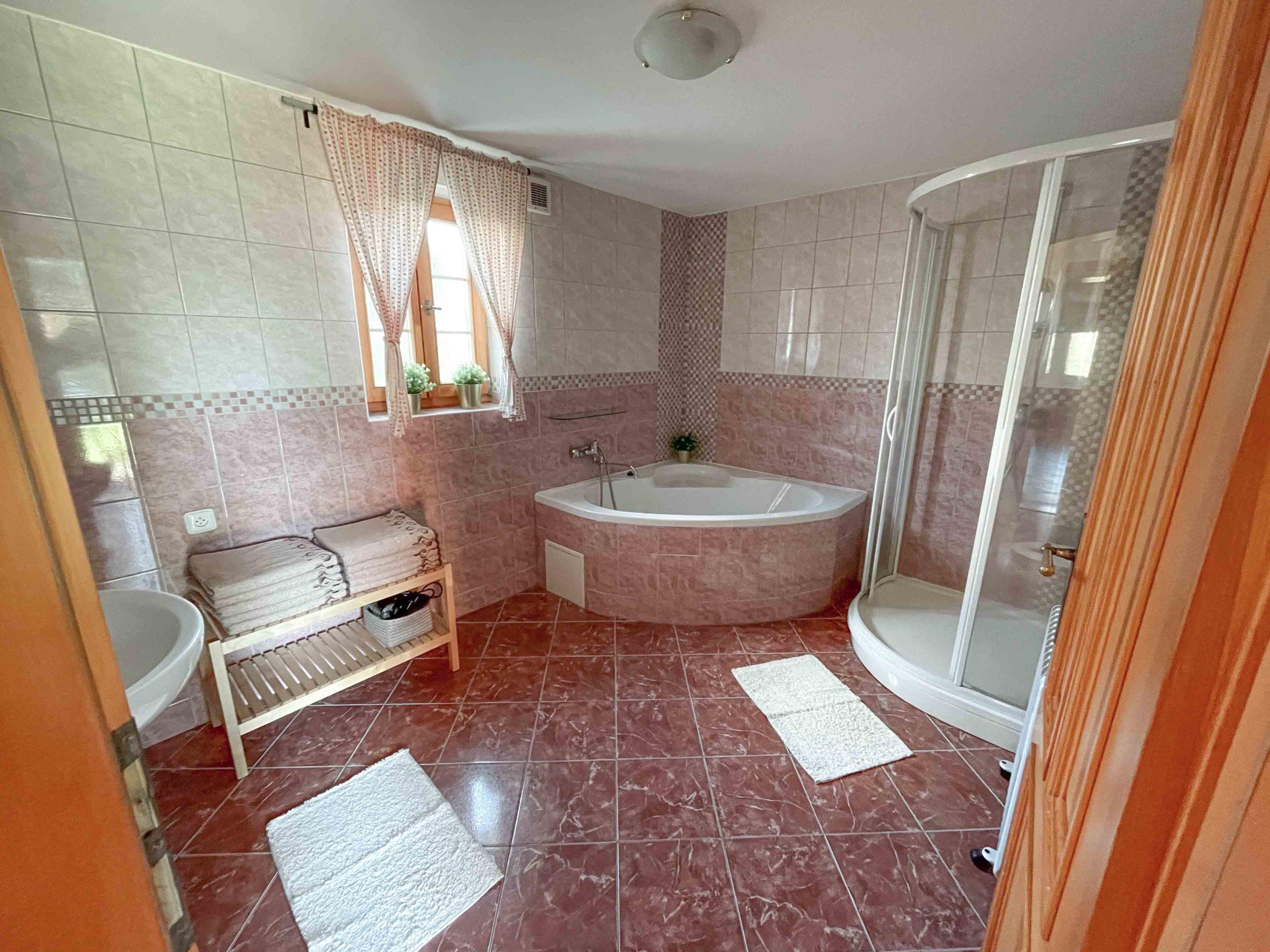 V koupelně se nachází rohová vana, sprchový kout, umyvadlo se zrcadlem a topení na ručníky. Celá koupelna je pak vytápěná podlahovým vytápěním.