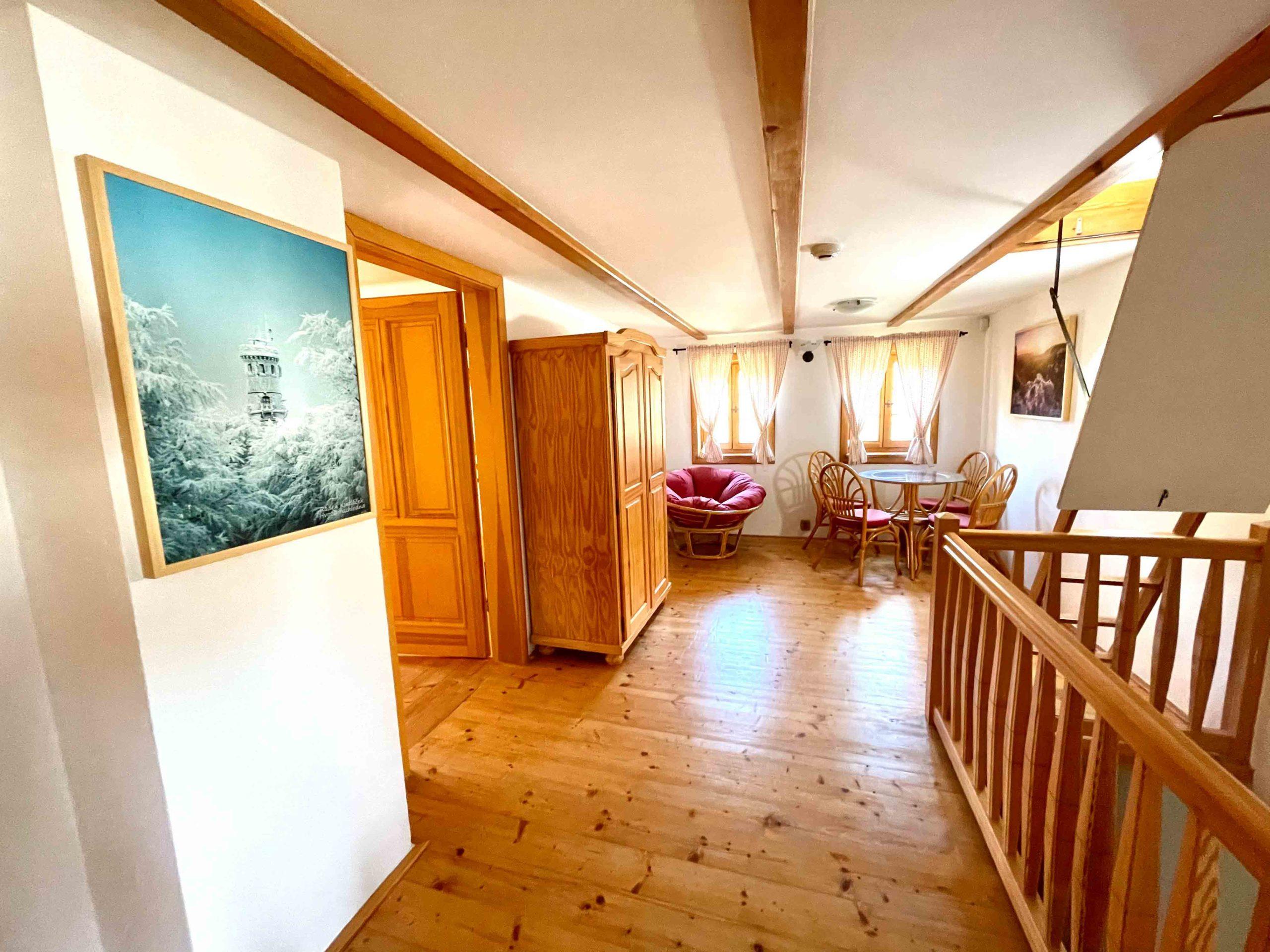 Chodba ve 2. patře s dveřmi do obou ložnic a společným posezením.